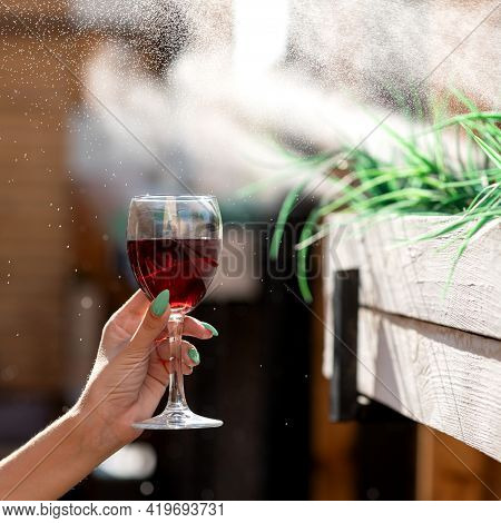 Female Hand Holding Glass With Red Wine On A Blurred Backlit Background With Sprayed Water Droplets.