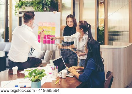 Business People Meeting Use Sticky Notes On Whiteboard In Office.  Teamwork Diverse Employees People