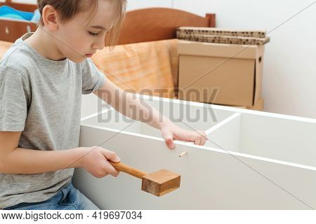 Boy Assembles A Bookshelf Hisself. Son Helping His Dad To Assembling New Furniture At Home.