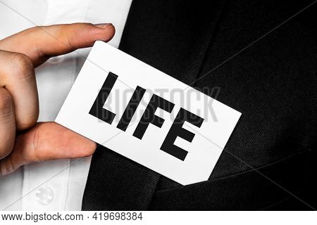 Inscription Life On A White Business Card. A Man In A Black Business Suit Lowers Or Removes From His