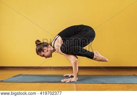 Woman Practicing Yoga, Doing Bakasana Exercise In Simplified Form, Crane Pose, Exercising On A Mat A