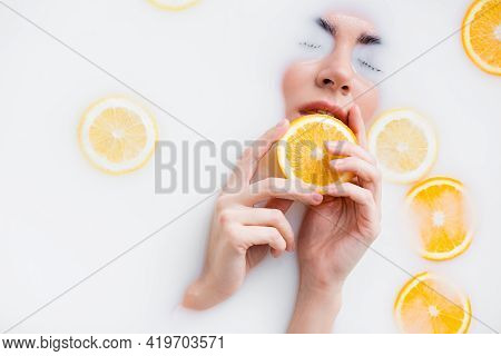 High Angle View Of Woman Holding Orange Slice While Immersing Face In Milk Bath.