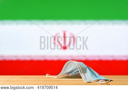 A Medical Mask Lies On The Table Against The Background Of The Flag Of Iran. The Concept Of A Mandat