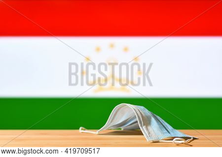 A Medical Mask Lies On The Table Against The Background Of The Flag Of Tajikistan. The Concept Of A