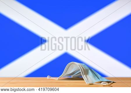 A Medical Mask Lies On The Table Against The Background Of The Flag Of Scotland. The Concept Of A Ma