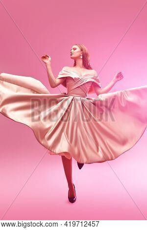 Attractive girl in a light pink legant evening dress with a neckline dancing at the studio in gentle pink light. Evening fashion.