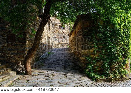 Small Alley With Stone Facades Covered By Green Ivy In Spring. Patones De Arriba Madrid. Spain.