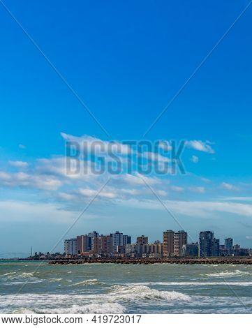 Plain Coastline With High Buildings And Blue Sky