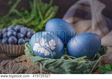 Natural dyed easter eggs on a wooden background. Colored with bluberries.