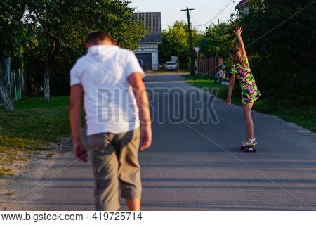 Defocus Happy Young Girl And Boy Playing On Skateboard In The Street. She Put Arms Up. Caucasian Kid