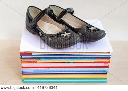 Close-up And Selective Focus Of Black Old Worn Children's Shoes On A Stack Of Books Lying On The Tab
