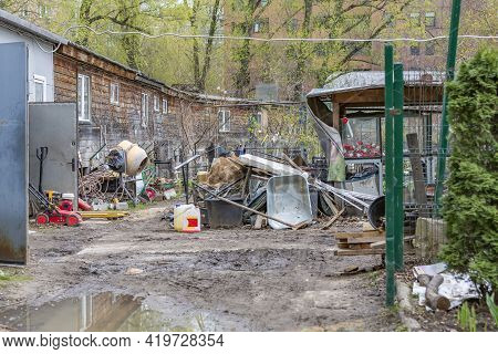 Littered Backyard Of An Abandoned Wooden House On The Outskirts Of The City