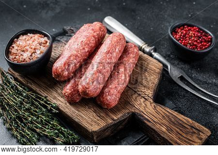 Uncooked Raw Beef And Lamb Meat Kebabs Sausages On A Wooden Board. Black Background. Top View