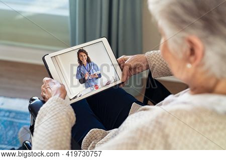Back view of senior woman sitting in wheelchair making video call with her doctor while staying at home during covid pandemic. Sick woman in online consultation from home: distance and tele health.