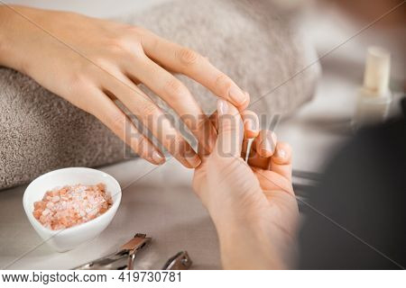 Close up of beautician hands doing hand treatment at nail salon. Woman holding the finger of customer during manicure. Detail of hands of manicurist massaging client fingers in manicure salon.