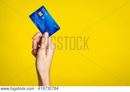 Close up of woman hand showing credit card on yellow background. Detail of female hand holding bank credit card against yellow wall with arm raised. Young woman showing creditcard with copy space.