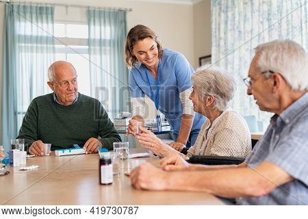 Nurse giving medicine to group of seniors at retirement community. Happy smiling nurse gives medicines to elderly patients at nursing home. Happy senior woman taking her dose of medicines.