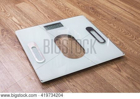 White Electronic Scales On A Wooden Floor Close Up