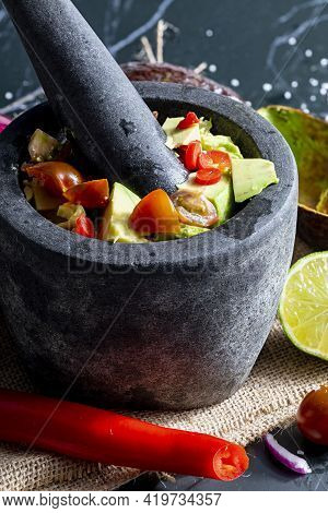 Preparation Of Guacamole In A Traditional Stone Mortar With All Its Ingredients (chopped Avocados, L
