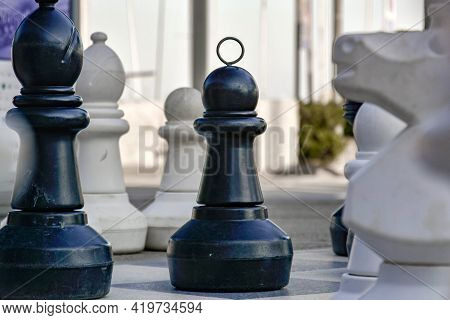 Chess Pieces On Board In Large Scale Outdoor Chessboard. Pawn, Bishop And Knight Fight For Winning T