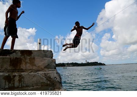 Salvador, Bahia, Brazil - June 5, 2015: Young People Are Seen Jumping Off A Pier At Santome Beach In