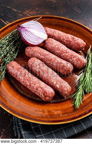 Raw Kofta Meat Kebabs Sausages On A Plate With Herbs. Dark Background. Top View