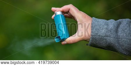 Young Woman Holding An Astma Inhaler Against Attacks In Her Hands, Healthcare Concept