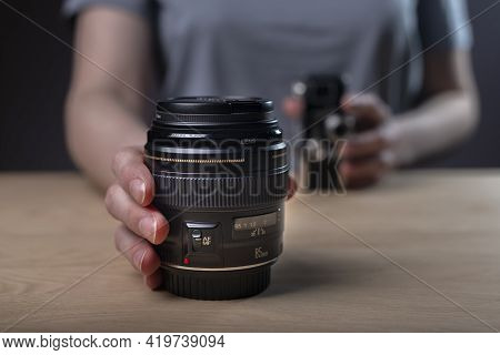 Photographer Showing Camera Lens, Blurred Vintage Old One And Modern 85 Mm Lens In Focus