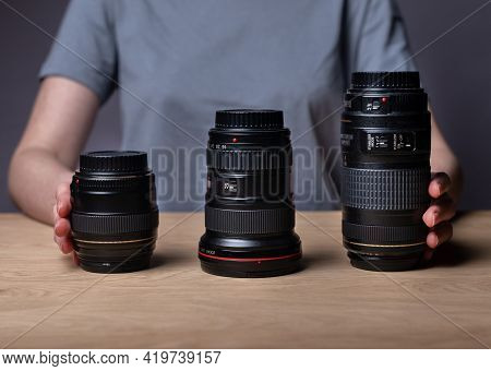 Different Camera Lenses On Wooden Table. 85 Mm, 35 Mm And 300 Mm. Various Modern Digital Lenses Of D