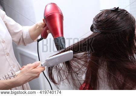 The Hairdresser Dries His Hair With A Hairdryer And A Massage Comb. Long Dark Hair. Spa Treatments F