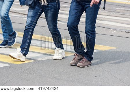 Pedestrians Cross The Street At A Pedestrian Crossing On Spring Day