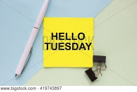 Top View Of A Business Card With Text Hello Tuesday, Pen, Paper Clips On A Colored Background. Busin