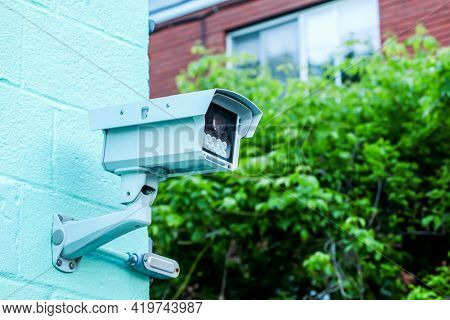 Survilence camera on building with blue sky