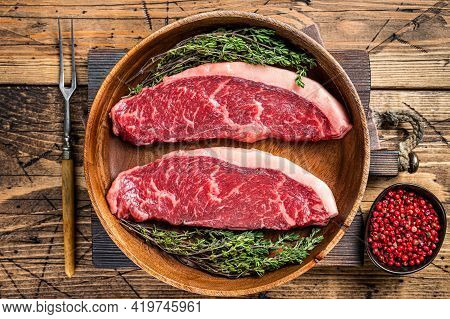 Uncooked Raw Top Sirloin Cap Beef Meat Steaks In A Wooden Plate With Herbs. Woden Background. Top Vi