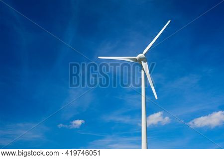 Green renewable alternative energy concept - wind generator turbines generating electricity in blue sky