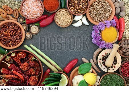 Herb and spice seasoning abstract border with fresh and dried herbs and spices on slate background with copy space. Flat lay.