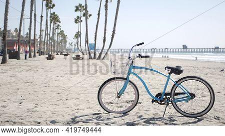 Blue Bicycle, Cruiser Bike By Sandy Ocean Beach, Pacific Coast Near Oceanside Pier, California Usa.