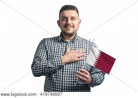 White Guy Holding A Flag Of Qatar And Holds His Hand On His Heart Isolated On A White Background Wit