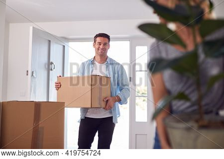 Excited Couple Carrying Boxes And Plant Through Front Door Of New Home On Moving Day