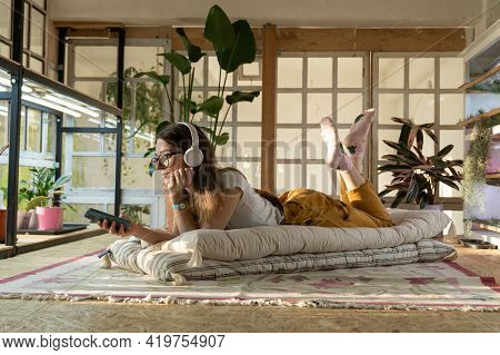 Female Gardener Relax After Work Lay On Floor, Listen Music And Surfing Internet On Smartphone App I