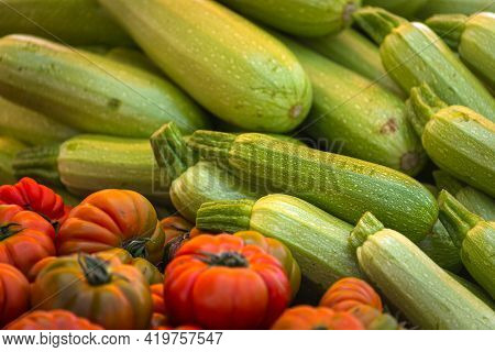 Tomatoes And Zucchini Background. Fresh Tomatoes And Green Zucchini Variety Grown In The Shop. Tomat