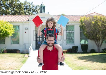Outdoor School. Father Giving Son Piggyback Ride After School. Schoolboy Going To School With Father