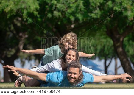 Family Lying On Grass In Park. Parents Giving Child Piggybacks In Countryside. Fly Concept, Little B