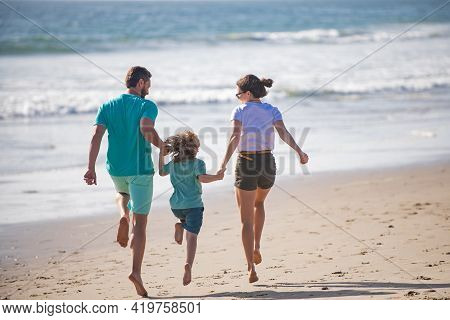 Happy Young Family Run And Jump On Summer Beach. Child With Parents Running And Jumping. Healthy Hol