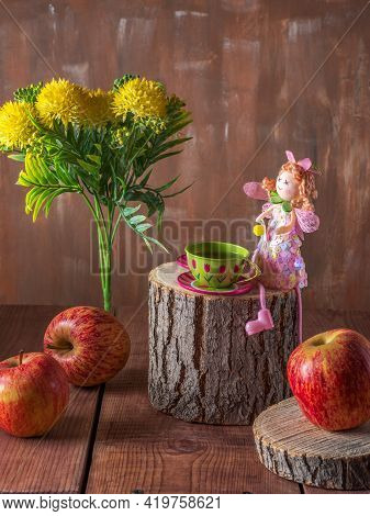 Congratulatory Fairytale Card With Apples And A Doll Fairy Sitting At A Table Made Of Wooden Hemp, A