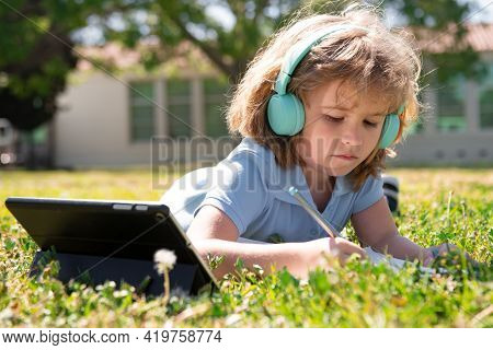 Child Homework Outside In Scholl Yard. Little Schoolboy Pupil With Tablet In The Park On Grass. Self