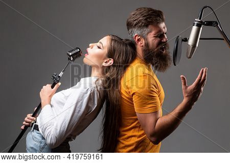 Couple Singing. Singing Man And Girl In A Recording Studio. Expressive Couple With Microphone. Karao