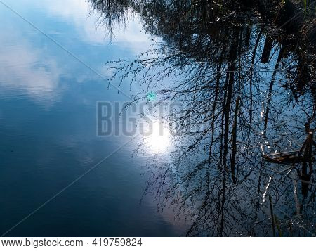 The Sun In The Blue Sky Is Reflected In The Water. Lakes And Rivers. Water Surface. Sun On A Blue Sk