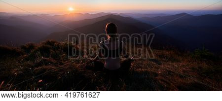 Back View Of Young Woman In Black Sportswear Doing Meditation In The Mountains At Sunset. Concept Of