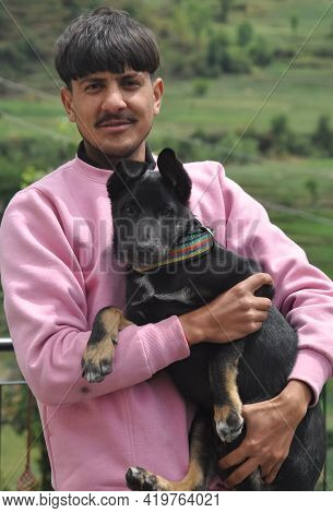Front View Of A Handsome Young Guy Standing Outdoor With Holding Black Color Dog In Hands